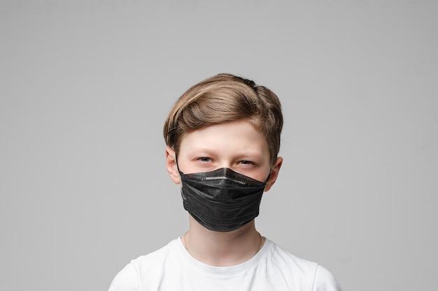 Adolescent se tient dans un masque médical noir, portrait isolé