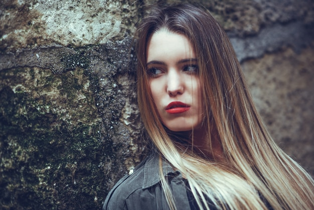 Adolescent sérieux avec les cheveux longs et les lèvres rouges