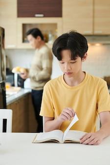 Adolescent sérieux, livre de lecture lorsque son père prépare le petit-déjeuner en arrière-plan