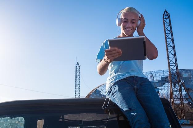 Un adolescent seul assis sur sa voiture à l'aide d'une tablette et écoutant de la musique avec des écouteurs - arrière-plan rural et urbain - concept technologique - cheveux blonds