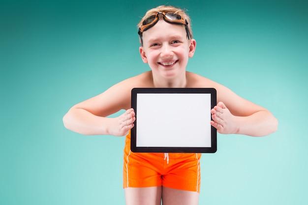 Adolescent en short orange et lunettes de natation détiennent une tablette vide