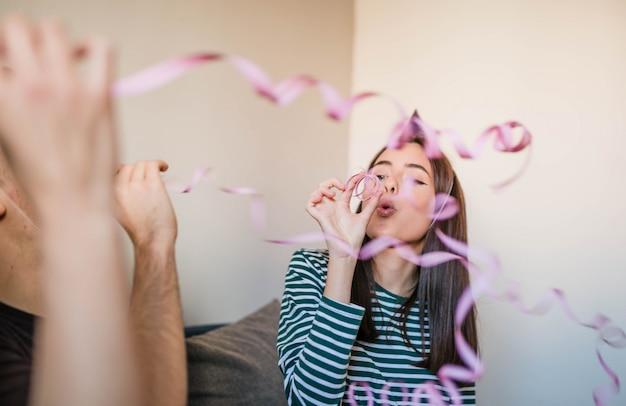 Adolescent soufflant des banderoles en papier