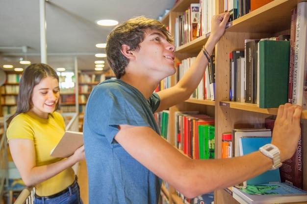 Adolescent souriant, choisir un livre près de la petite amie