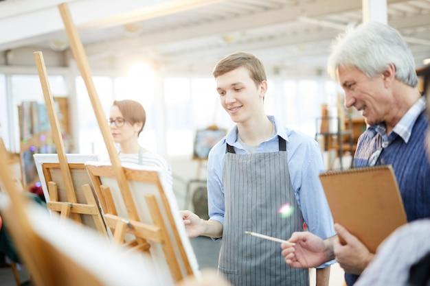 Adolescent souriant en classe d'art