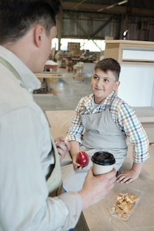 Adolescent souriant en tablier assis sur la table et manger des pommes tout en discutant avec le père pendant la pause en atelier