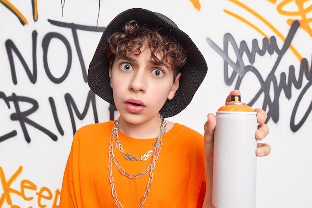 Un adolescent surpris a l'air choqué à la caméra détient un vaporisateur de bouteille aérosol aime créer des œuvres d'art contemporain sur les murs de la rue porte des vêtements à la mode mène le style de vie urbain