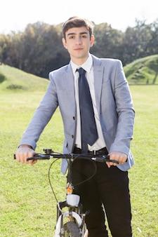 Adolescent tenant son vélo dans le jardin