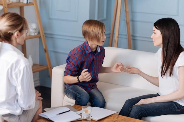 Adolescent têtu portant des vêtements décontractés ayant une coupe de cheveux élégante à la colère sur maman