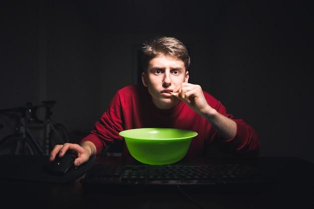 Adolescent tient une souris dans la main et regarde l'écran d'ordinateur