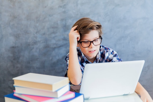 Adolescent travaillant sur ordinateur portable à la maison