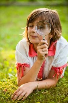 Un adolescent utilise une loupe pour découvrir la nature