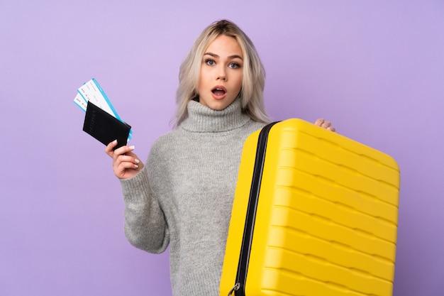 Adolescent en vacances avec valise et passeport et surpris