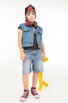 Adolescent en veste en jean et snorts, casquette noire, avec un sou jaune, isolé