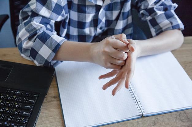 Un adolescent vêtu d'une chemise à carreaux en train de s'entraîner à domicile a déchiré une feuille d'un cahier et la froisse dans ses mains.