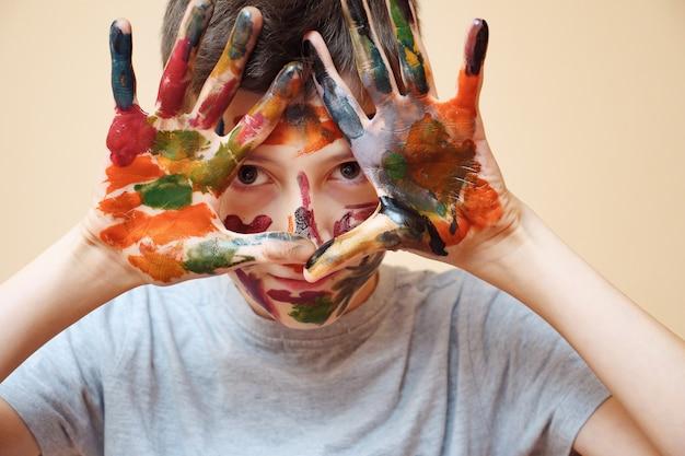 Adolescent avec visage et paumes couvertes de peintures vives