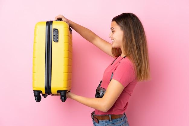 Adolescent voyageur femme tenant une valise sur un mur rose isolé avec une expression heureuse