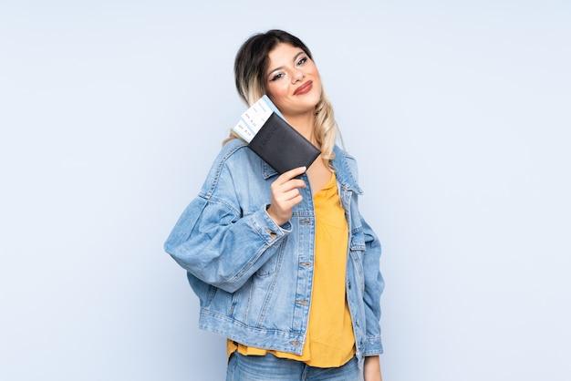 Adolescent voyageur tenant une valise isolée sur le mur bleu heureux en vacances avec passeport et billets d'avion