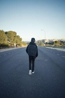 Adolescent vu de derrière une route vide
