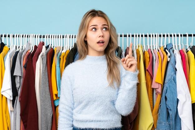 Adolescente, acheter des vêtements sur le mur bleu dans l'intention de réaliser la solution tout en levant un doigt