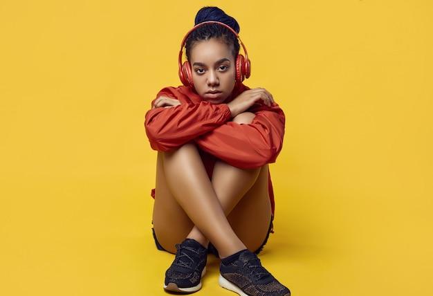 Adolescente africaine avec des dreadlocks en musique coupe-vent rouge
