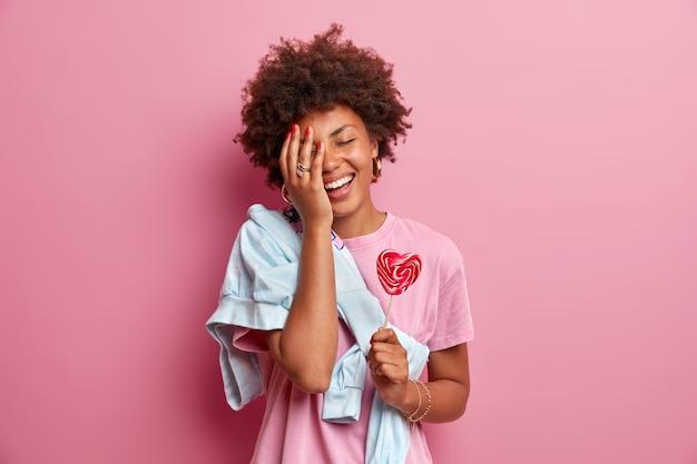 Une adolescente afro-américaine positive fait face à la paume, s'amuse, vêtue de vêtements décontractés, tient une sucette en forme de coeur, aime le temps libre, pose contre le mur rose. concept de confiserie