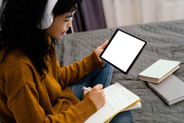 Adolescente à l'aide de tablette pour l'école en ligne