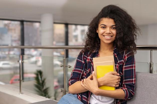 Adolescente à angle élevé avec une pile de livres