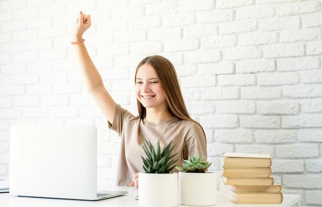 Adolescente apprenant de la maison assis au bureau avec le bras levé