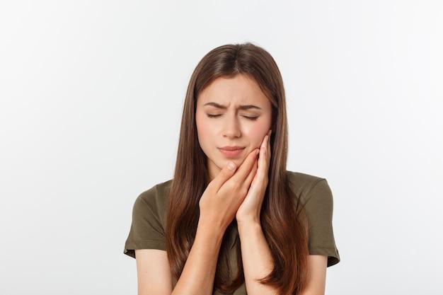 Adolescente appuyant sur sa joue meurtrie avec une expression douloureuse comme si elle avait un terrible mal de dents