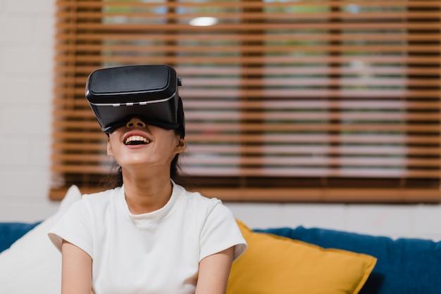 Adolescente asiatique à l'aide de lunettes simulateur de réalité virtuelle, jeux vidéo dans le salon