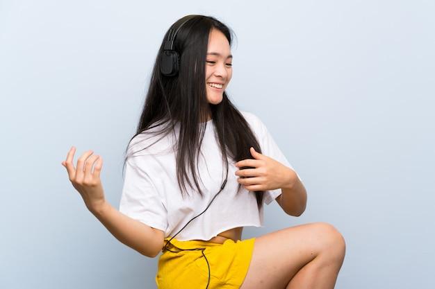 Adolescente asiatique écoute de la musique sur un mur bleu isolé