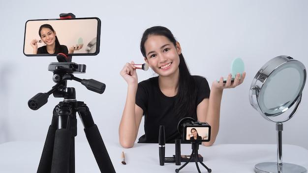 Une adolescente asiatique est assise devant la caméra et diffuse en direct en tant qu'influenceuse blogueuse beauté ou youtubeuse pour revoir ou donner des conseils sur la façon de se maquiller à la maison.