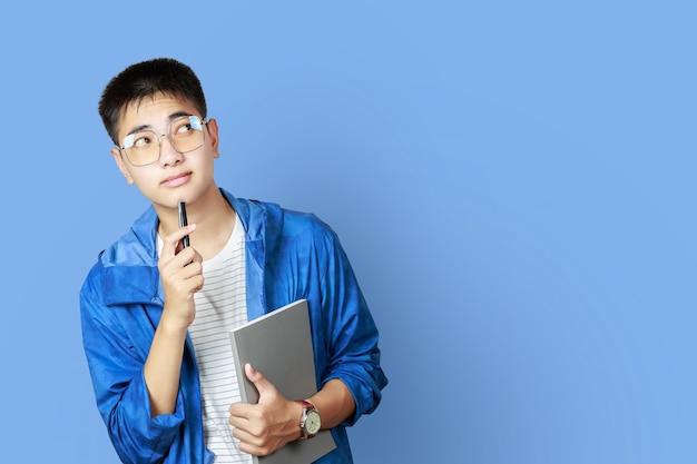 Adolescente asiatique à la recherche et doigt pointé vers copyspace