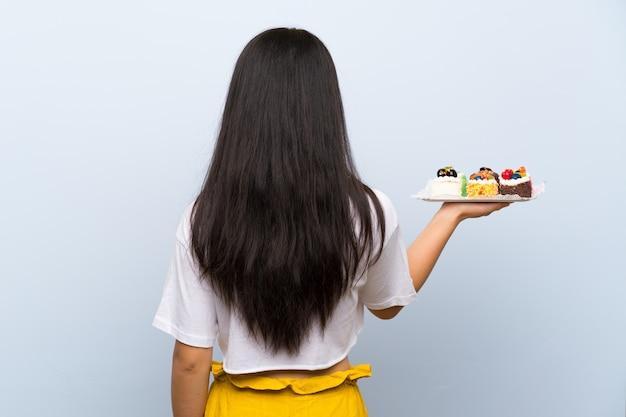 Adolescente asiatique tenant beaucoup de mini gâteaux différents en position arrière