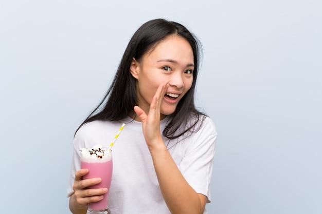 Adolescente asiatique tenant un milkshake à la fraise murmurant quelque chose