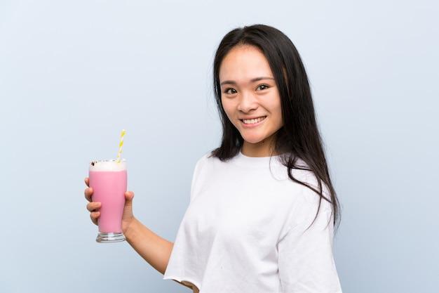 Adolescente asiatique tenant un milkshake à la fraise souriant beaucoup