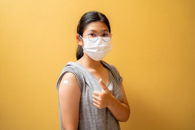 Une adolescente asiatique vaccinée dans un masque facial montrant un pansement en plâtre sur son bras après avoir reçu une injection de vaccin covid-19 sur fond de studio jaune. campagne de vaccination de la population contre le coronavirus