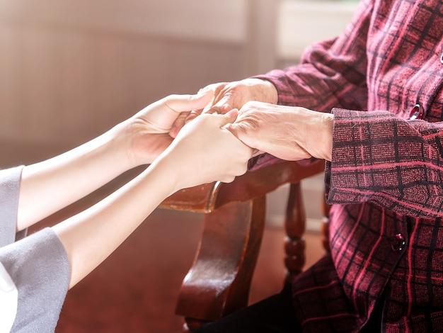 Adolescente asie jeune fille soignant tenant les mains de grand-mère, concept d'aide aux soins pour les personnes âgées avec fond sombre, gros plan, espace copie, vue recadrée