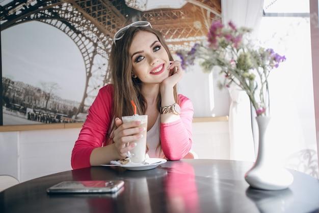 Adolescente assis à une table en verre avec un smoothie chocolat