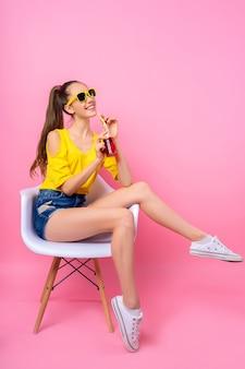 Adolescente assise sur une chaise et buvant une boisson