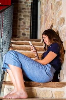 Adolescente assise dans les escaliers en regardant le téléphone.