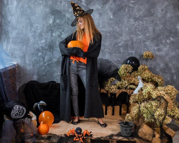 Adolescente au chapeau parmi le décor pour les vacances d'halloween, énorme citrouille à la main. photo pleine longueur