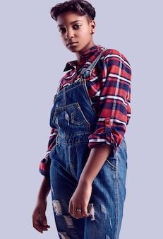 Adolescente aux cheveux courts dans une chemise à carreaux et une salopette en jean