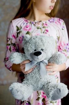 Adolescente aux cheveux longs blonds dans une robe rose tenant un ours en peluche gris lumière naturelle mise au point sélective