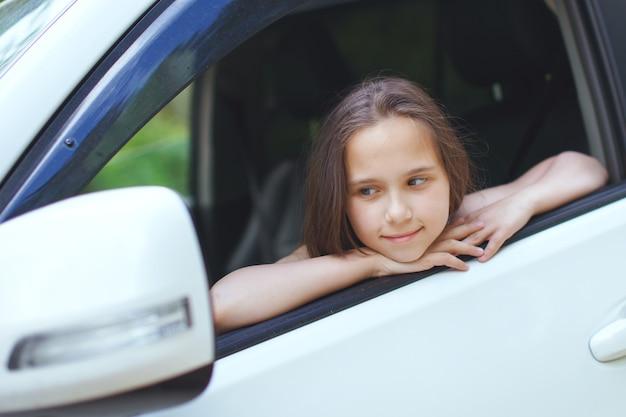 Une adolescente aux cheveux longs regarde par la fenêtre de la voiture.