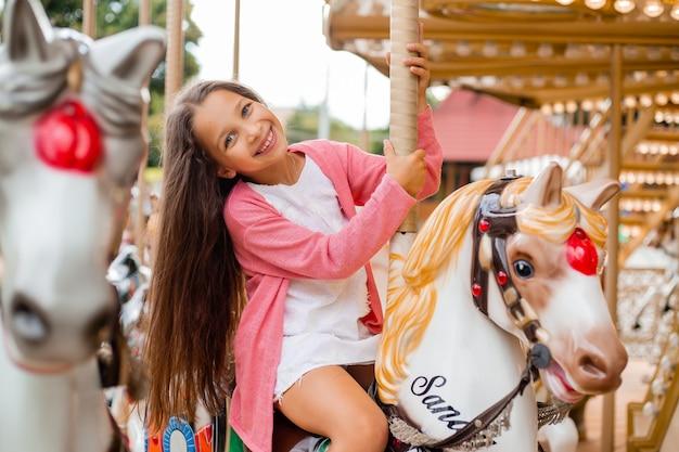 Une adolescente aux cheveux longs roule sur un carrousel à cheval. assis sur un cheval dans un parc d'attractions