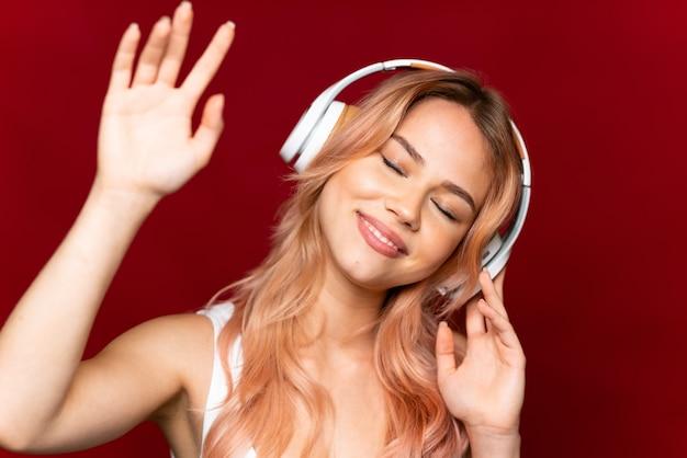 Adolescente aux cheveux roses sur mur rouge isolé, écouter de la musique et de la danse