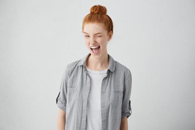 Adolescente aux cheveux rouges enfantin et ludique clignant des yeux, gardant la bouche grande ouverte