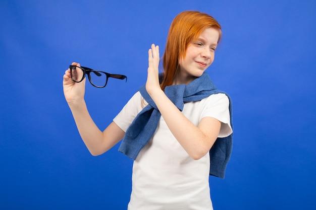 Une adolescente aux cheveux roux dans un t-shirt blanc jette des lunettes bleues. nouvelle vision