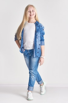 Adolescente blonde en costume de denim, amusant enfant qui pose de la mode